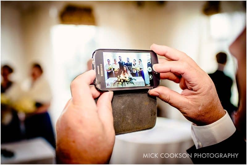 wedding guest takes photo on their phone