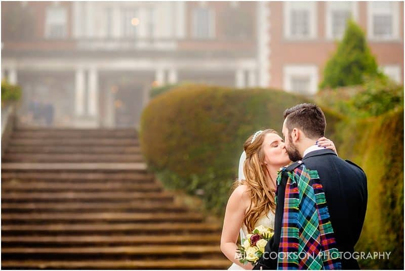 bride and groom pose outside eaves hall in the mist