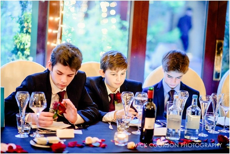 three boys on mobile phones at a wedding