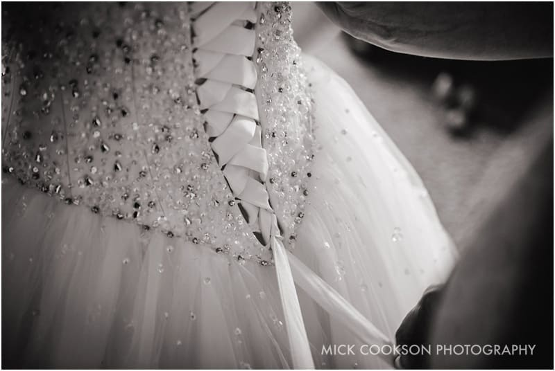 wedding dress being fastened
