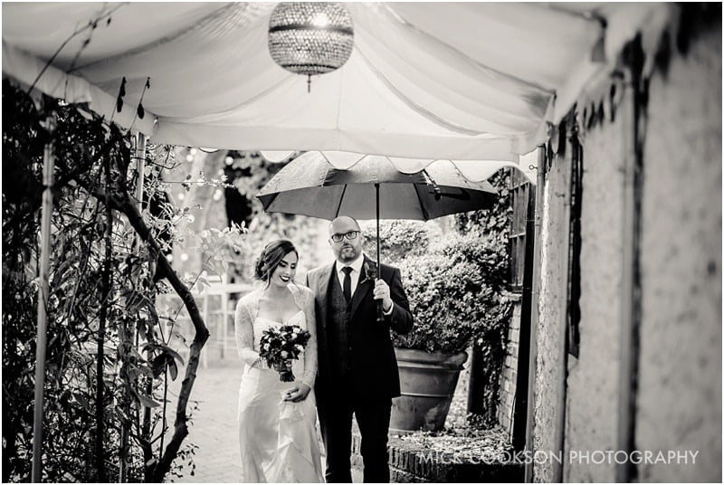bride and groom in the rain at the crazy bear stadhampton