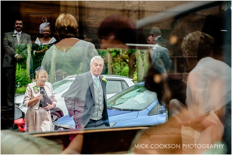 wedding guests reflected in a car window