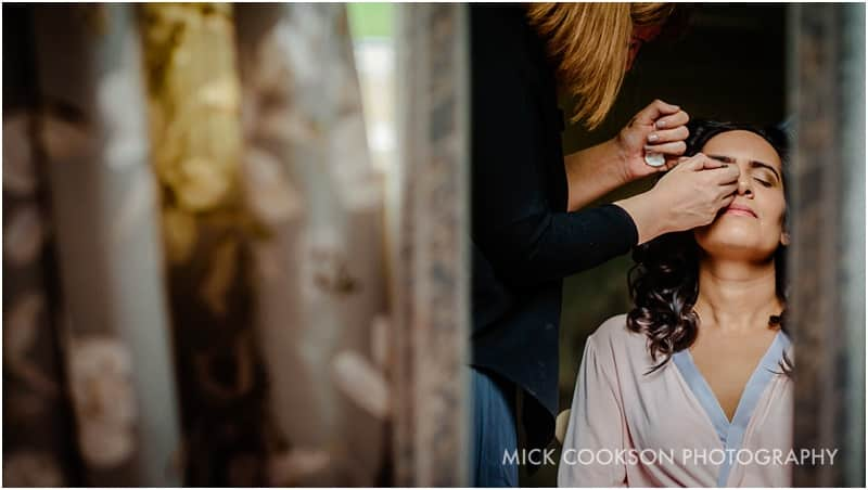 bride having her makeup applied at a wedding