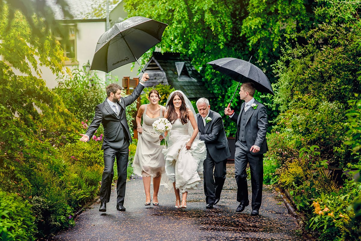 bride walking to church in the rain