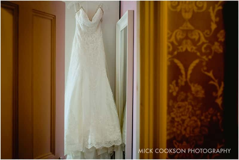 stunning wedding dress hanging in a bedroom