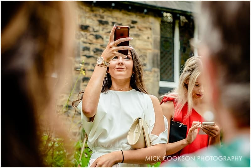 wedding guest taking a photo on her phone