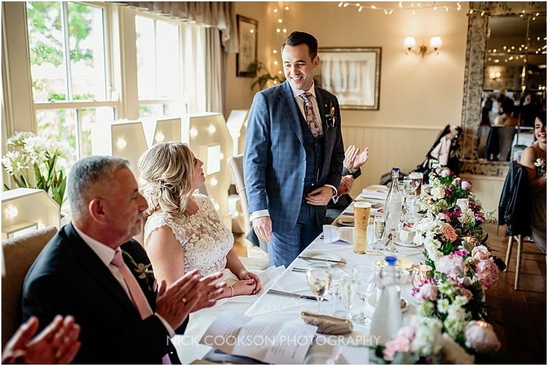 groom looks at his bride during his speech
