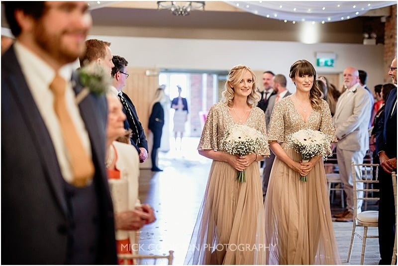 bridesmaids smiling down the aisle