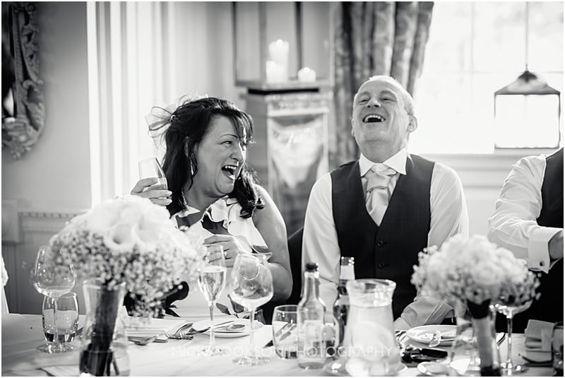 mum and dad laughing at the wedding speeches