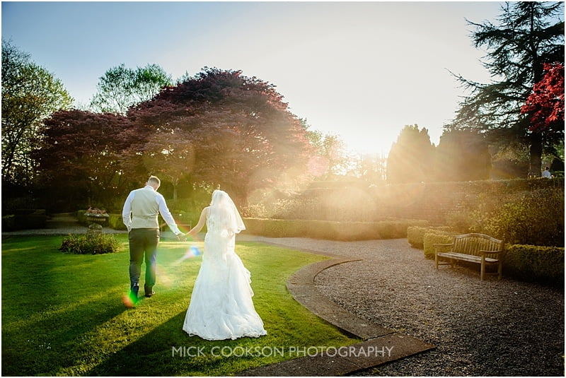 bride and groom strolling through the gardens at evaes hall