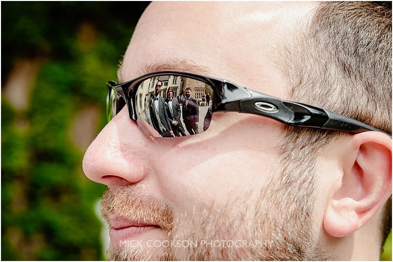 reflection of the groomsmen in the groom's sunglasses