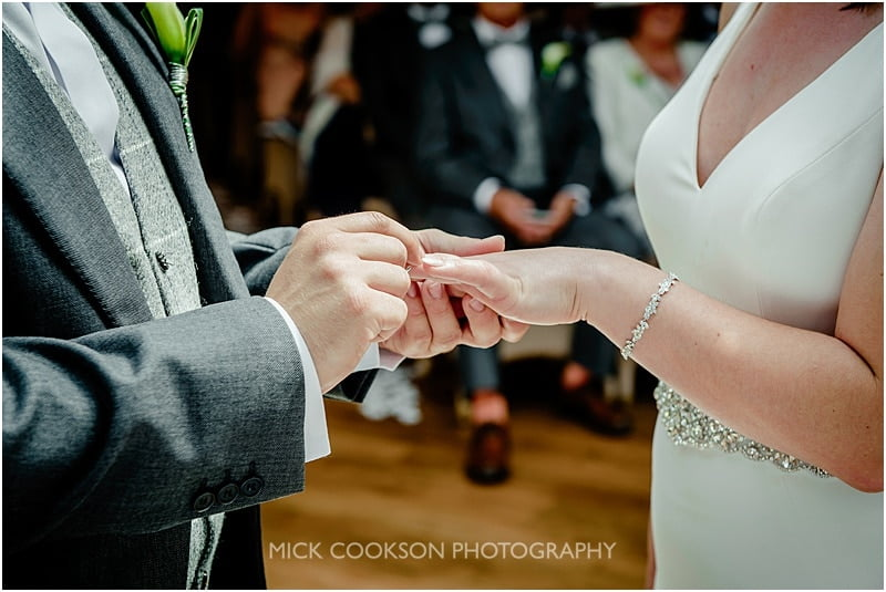 the wedding ring goes on at a mitton hall wedding