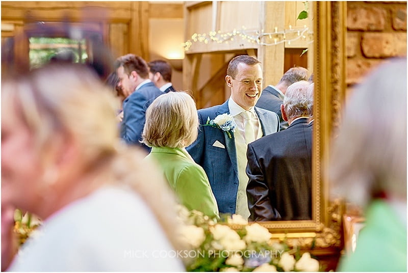 grrom reflected in a mirror at his oak tree of peover wedding