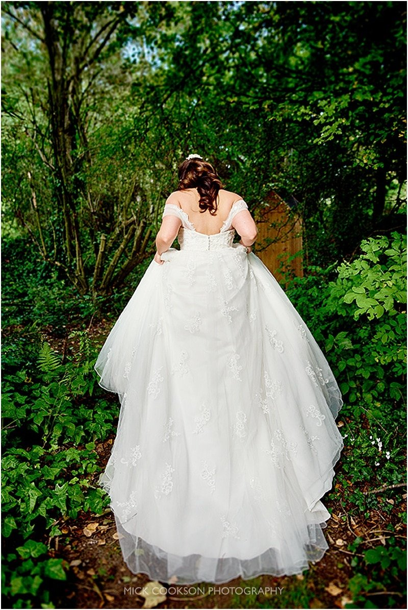 bride shows off her dress at her oak tree of peover wedding