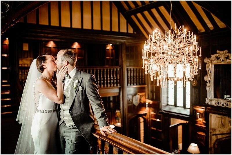 bride and groom kissing next to the fmous chandelier at mitton hall taken by manchester wedding photographer mick cookson