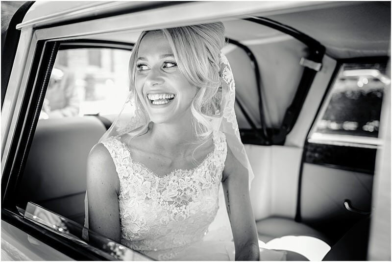 excited bride arriving in her wedding car for her church wedding