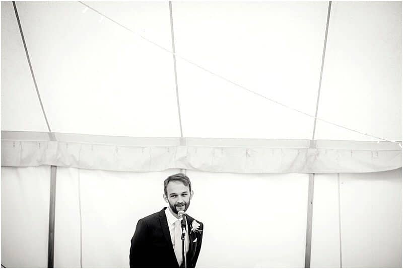 stylish best man speech wedding photo in a marquee taken by manchester wedding photographer mick cookson