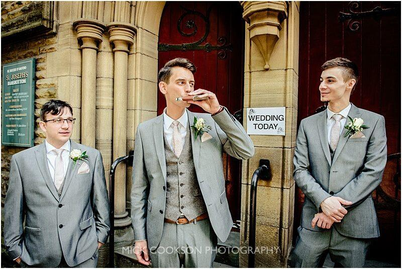 groom drinking from his hip flask outside church