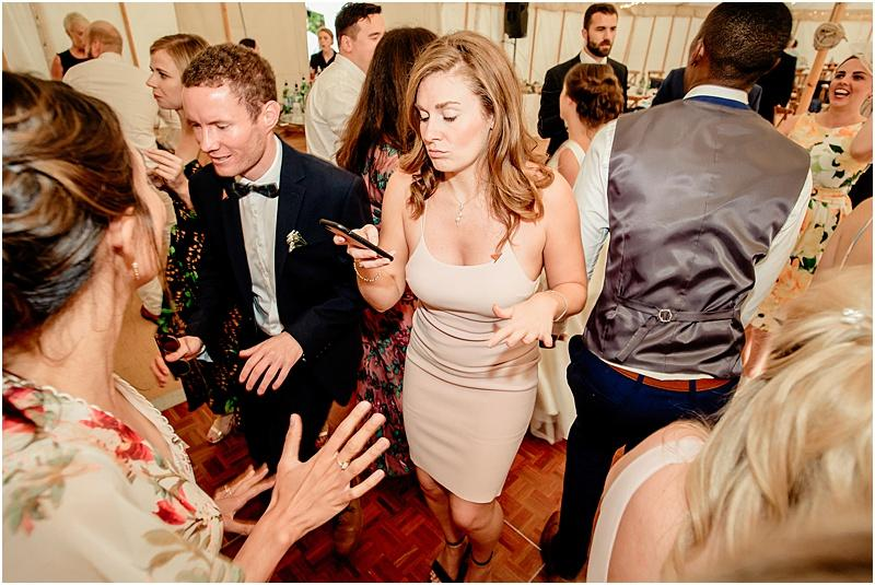 wedding guest on phone as she dances