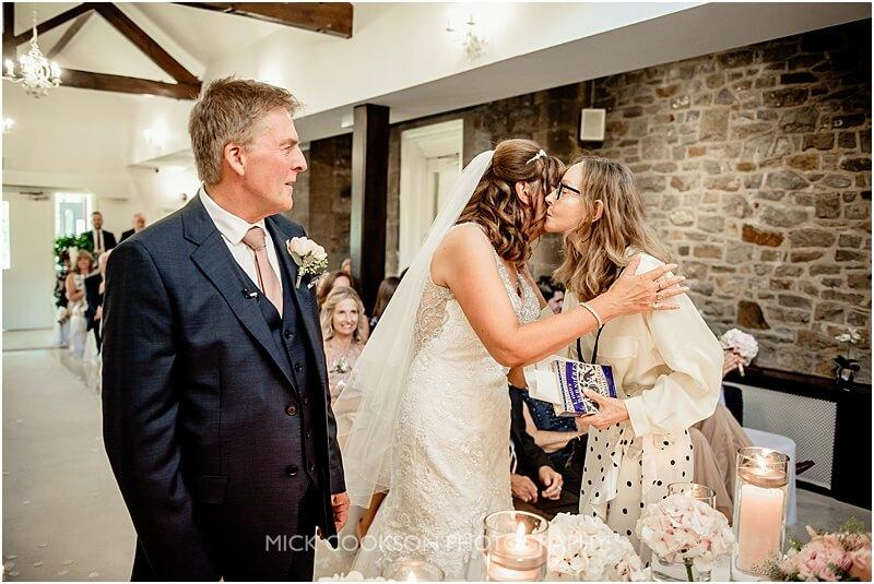 bride kisses a friend at stirk house