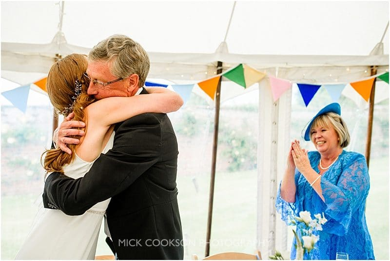 father of the bride hugs his daughter at a marquee wedding in york
