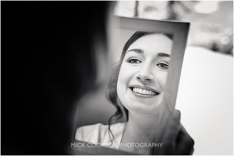 bride admires her makeup in a mirror