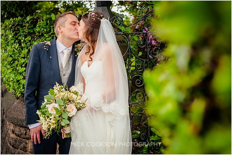 bride and groom kissing at the lych gate