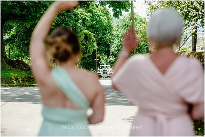 brides car approaches the bridesmaids