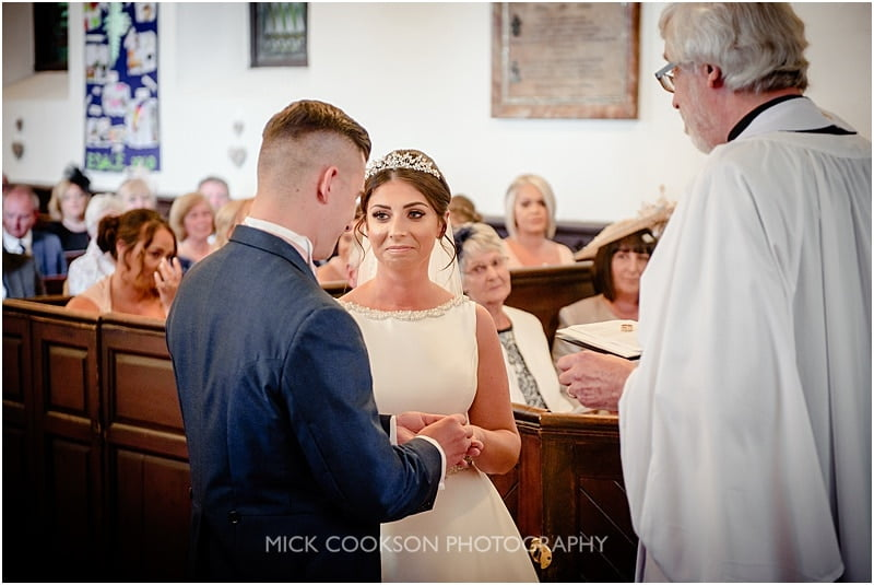 groom puts the ring on his brides finger