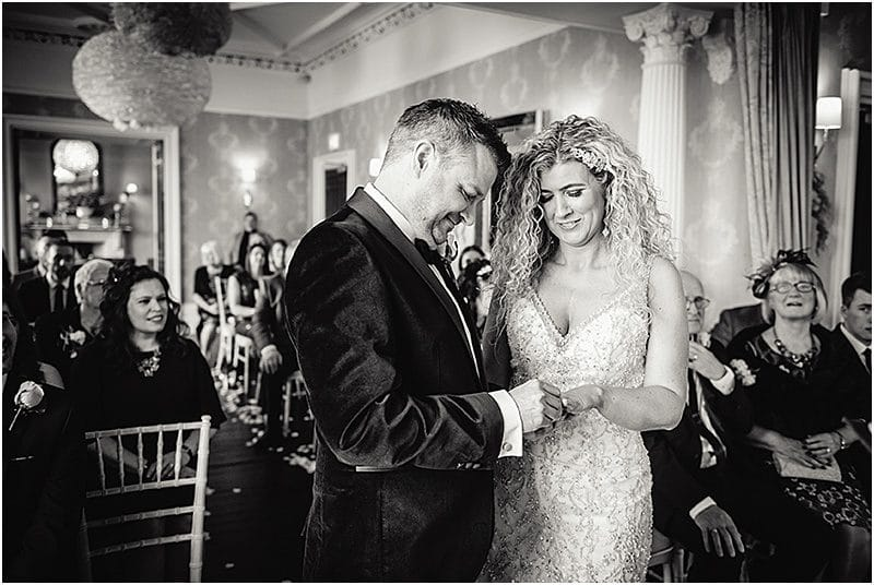 putting on the ring at a falcon manor wedding