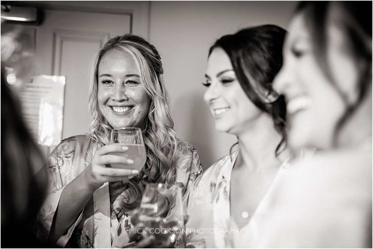 the bride shares a toast with the bridesmaids at the white hart at lydgate