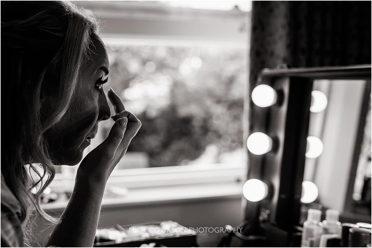 black and white photo of a bride having her makeup applied