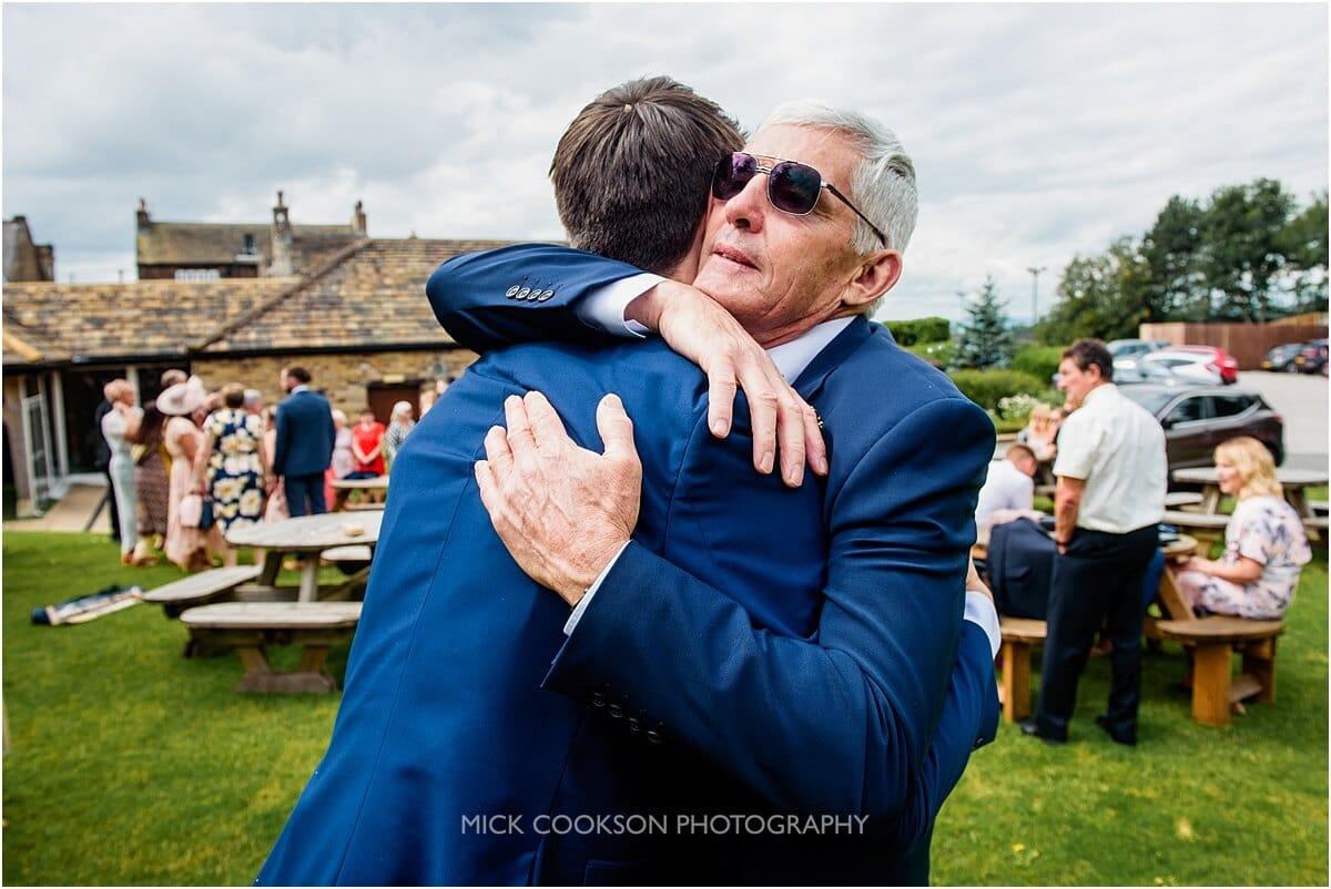 father hugs the groom at the white hart at lydgate