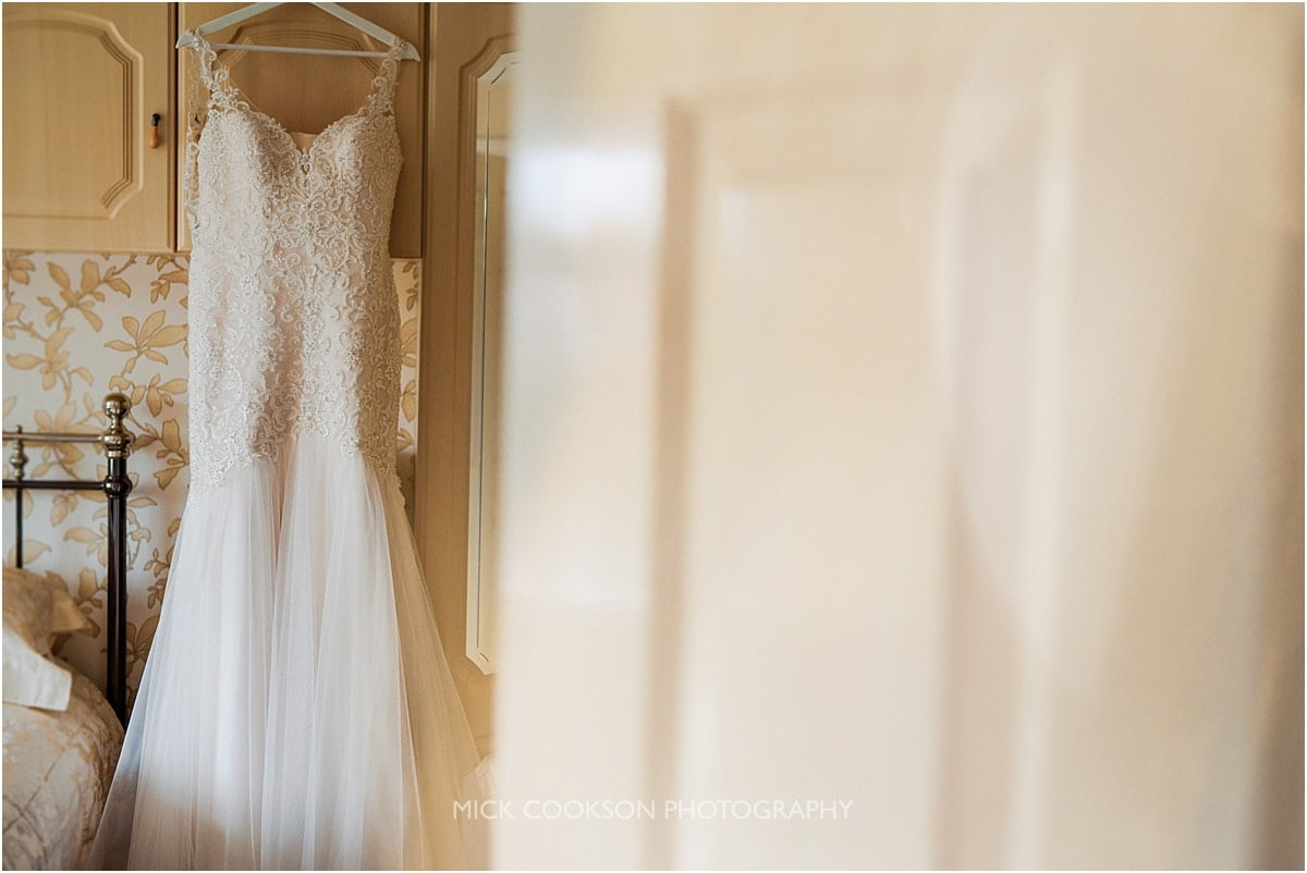 wedding dress hanging in a bedroom