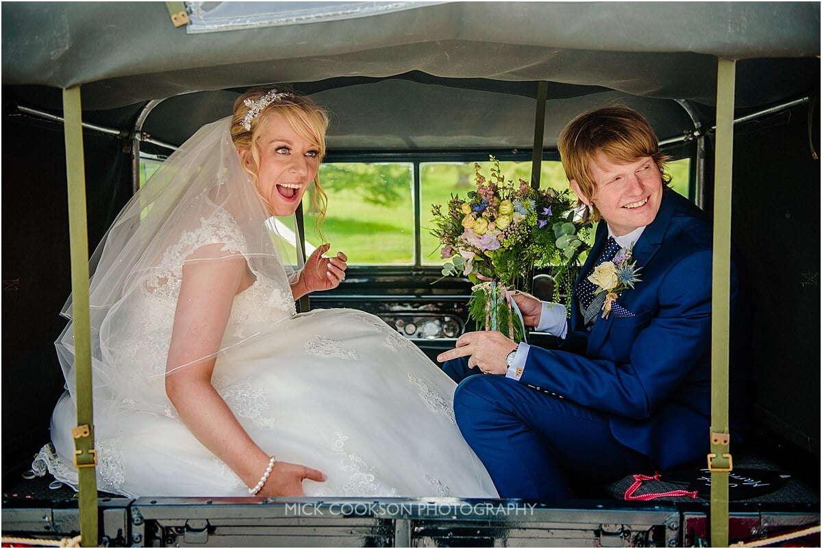 bride and groom arrive in a landrover