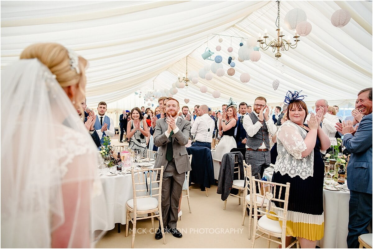 wedding guests applauding in a marquee