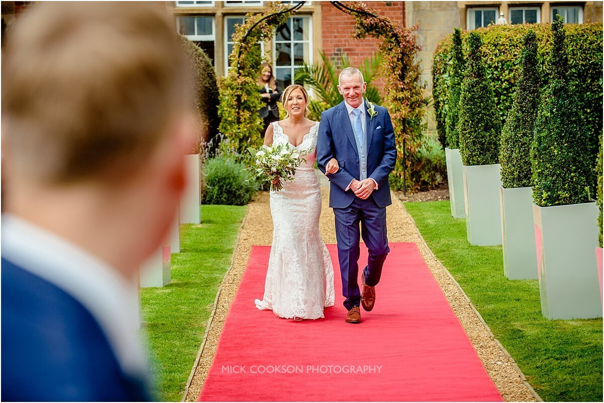 bride walks down the aisle with her dad at cranage hall