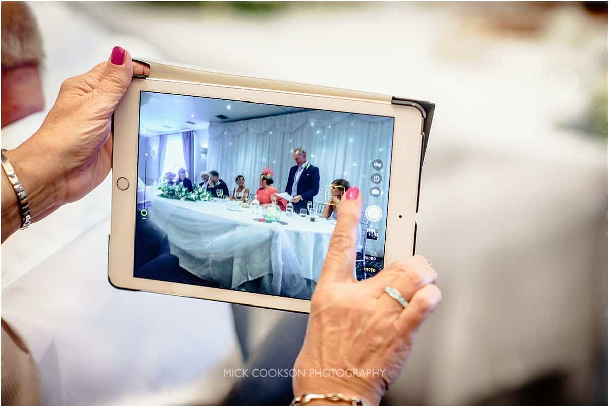 wedding guest recording the speeches on an ipad