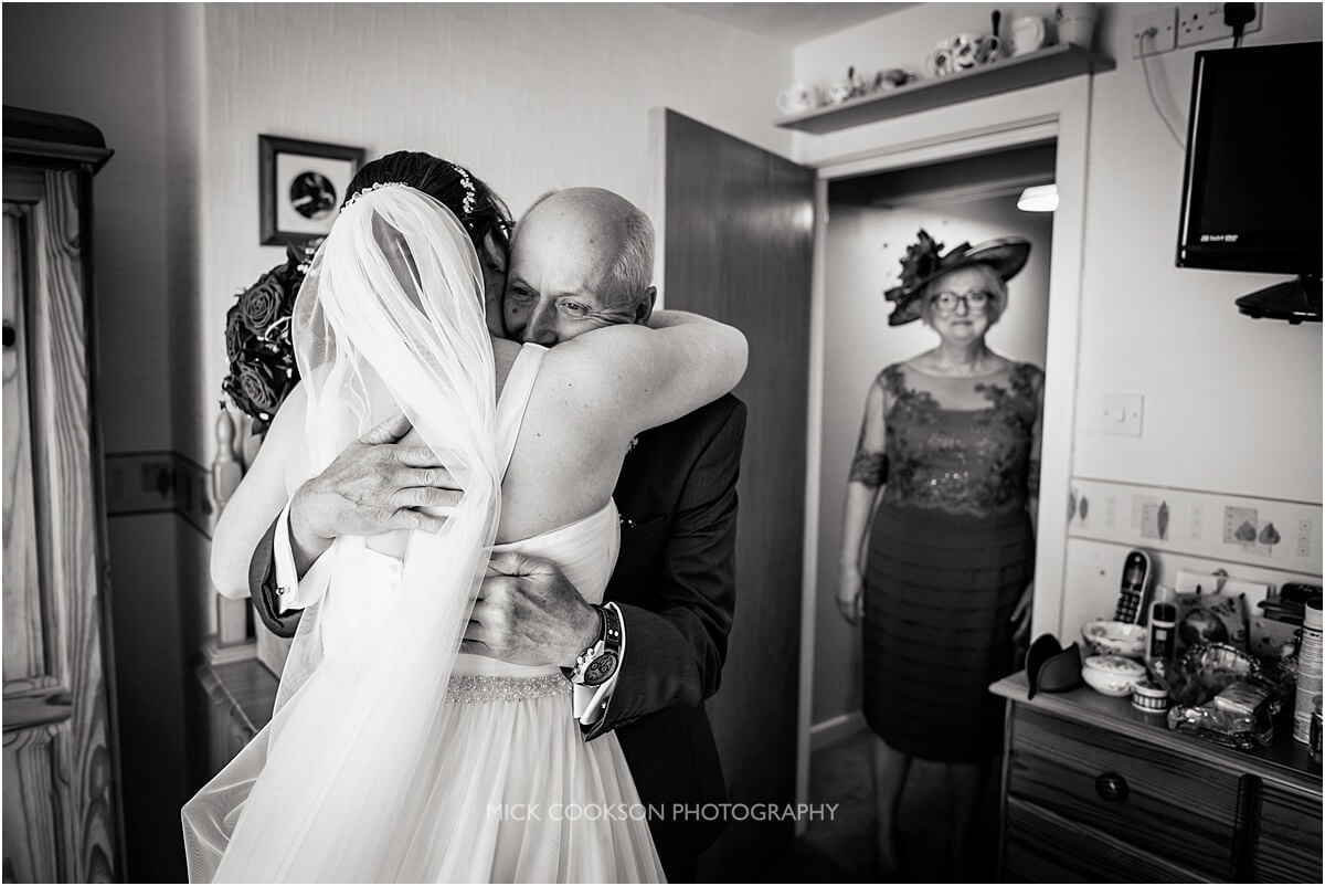 fatherof the bride hugs his daughter on their wedding day