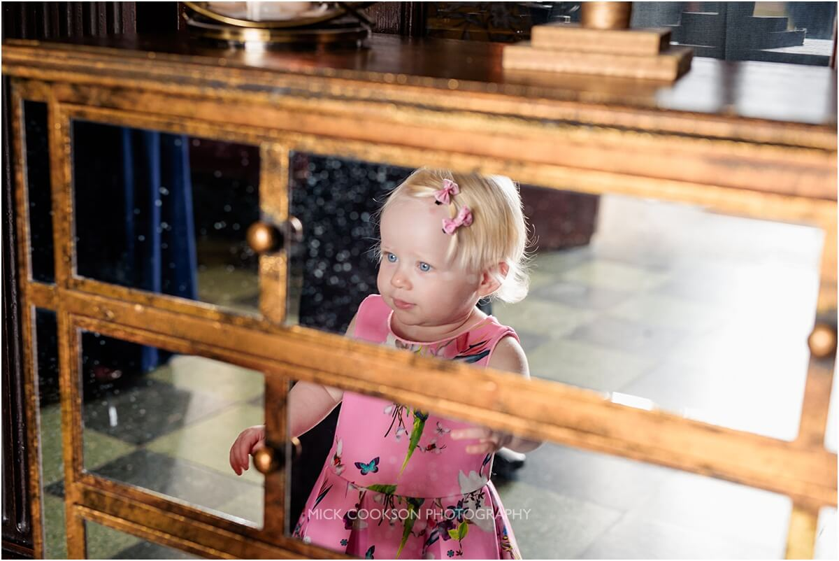 little girl looks at herself in a mirror