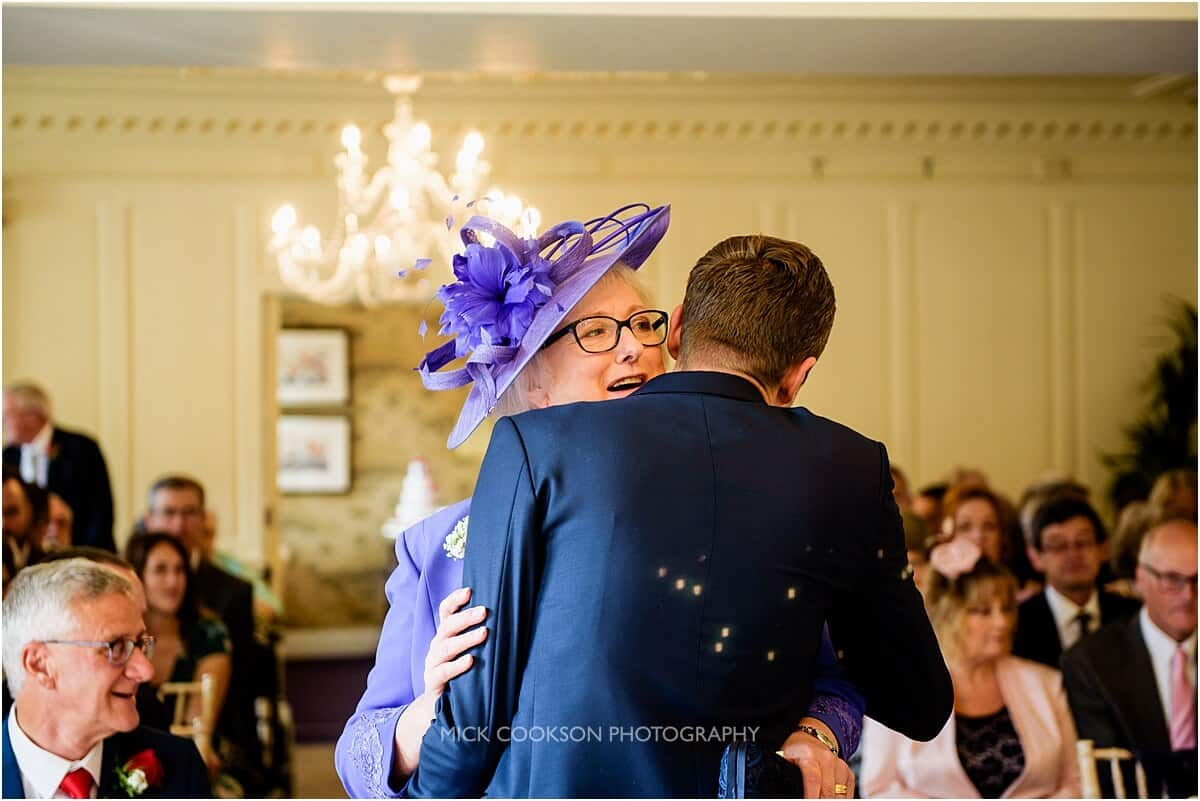 mother of the bride kisses the groom