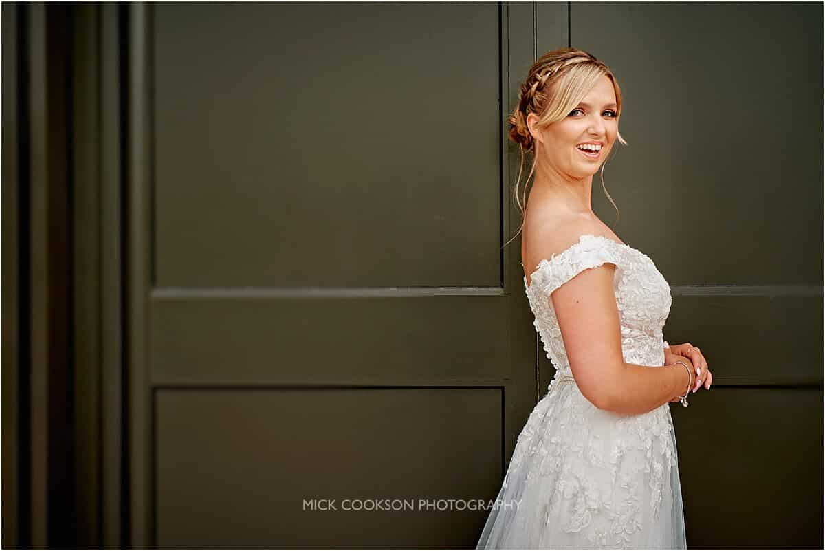 bride standing against a metal wall